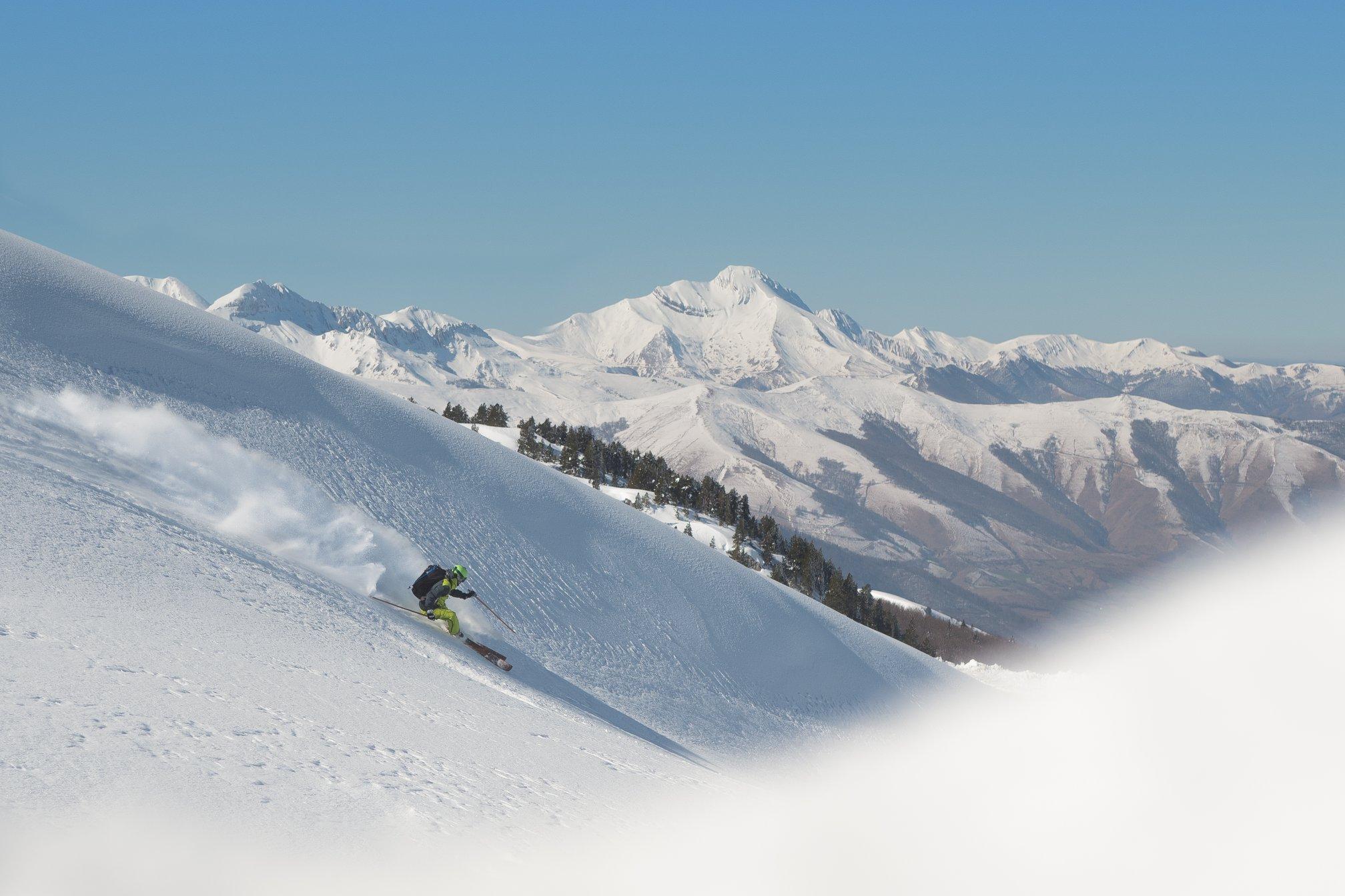 skieur descendant une face enneigée à La Pierre St martin, avec une montagne en fond