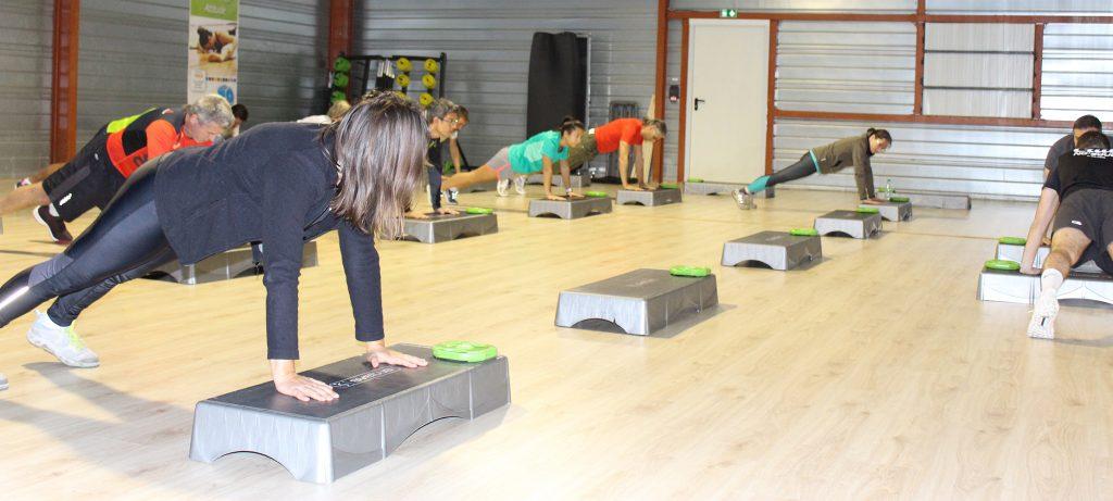 plusieurs personnes faisant des pompes pendant un cours de sport en groupe à la salle de l'orange bleue pau