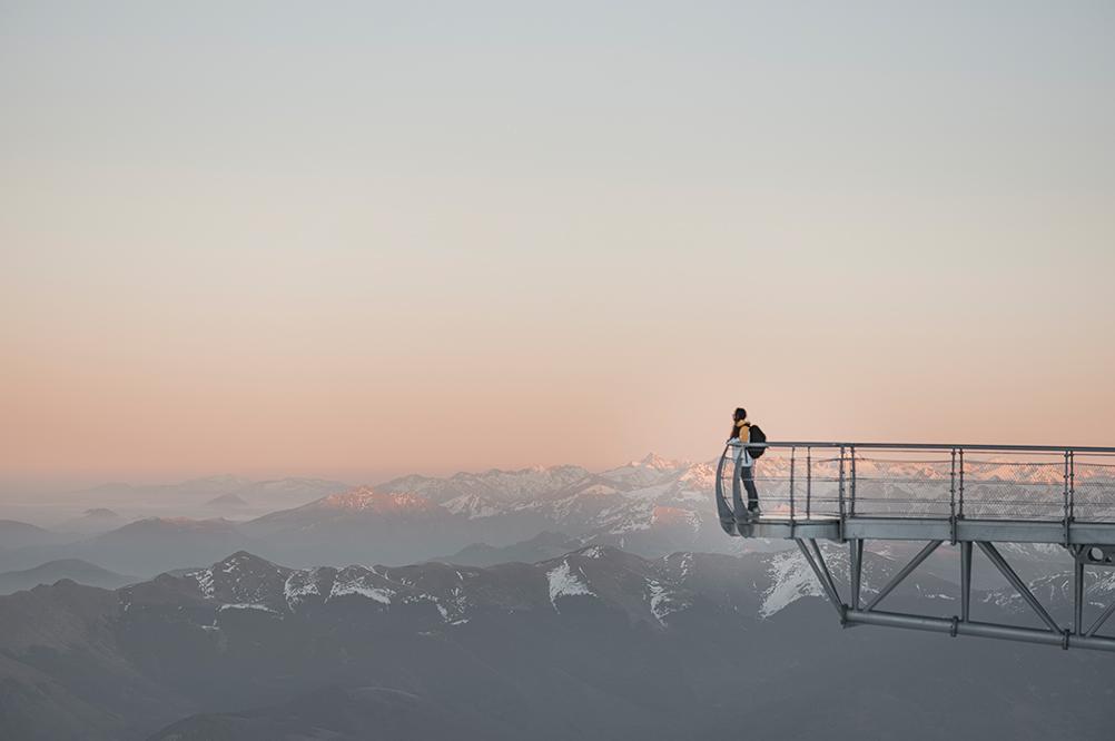 ponton du pic du midi avec coucher de soleil en arrière plan, et un personne seule au bout du ponton